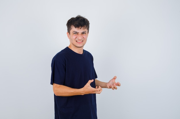 Brunette man keeping hands in aggressive manner in t-shirt and looking stressed , front view.