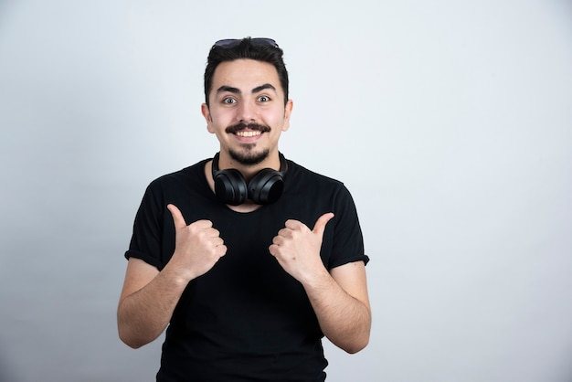 Brunette man model standing in headphones and showing thumbs up against white wall .