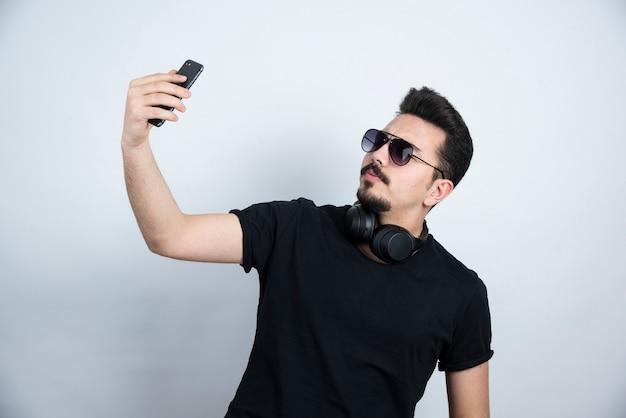 Modello di uomo castana in piedi in cuffie e prendendo selfie.