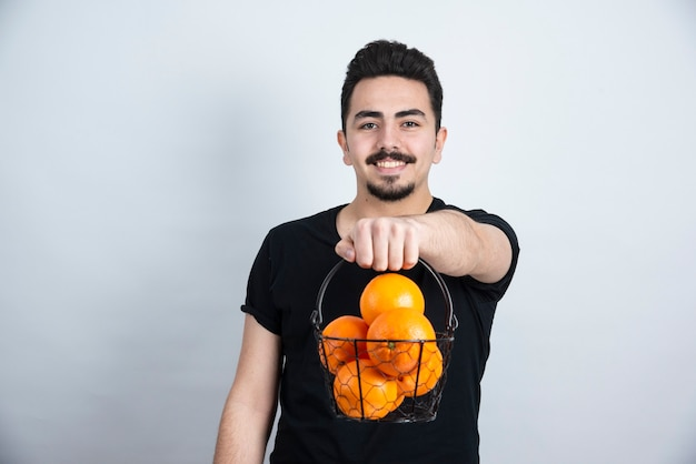 Brunette man model standing and holding metallic basket with orange fruits .
