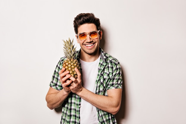 Brunette man in orange glasses and plaid green shirt is smiling and holding pineapple on white space.