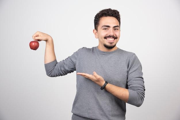 Uomo castana che indica alla mela rossa su gray.