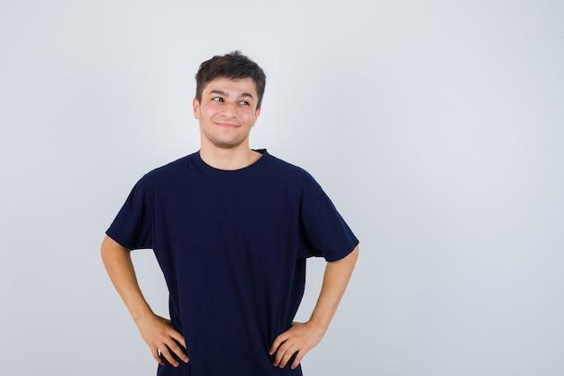 ブルネットの男性は、tシャツを着て腰に手を当ててポーズをとって陽気に見えます。正面図。