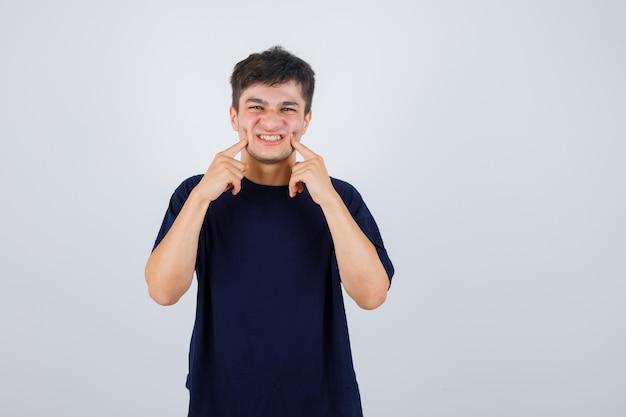 Uomo castana che preme le guance con le dita in maglietta e sembra divertente. vista frontale.