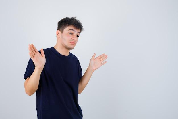 Брюнетка мужчина показывает беспомощный жест в футболке и выглядит озадаченным, вид спереди.