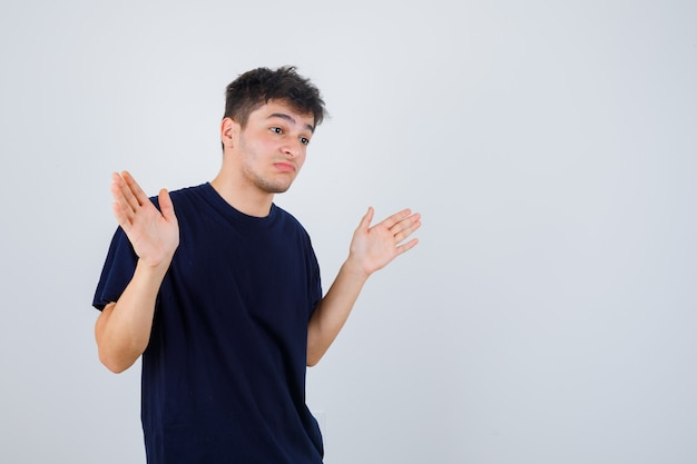 Brunette man showing helpless gesture in t-shirt and looking perplexed , front view.
