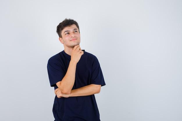 Uomo castana in maglietta che tiene la mano sotto il mento e che sembra pensieroso, vista frontale.