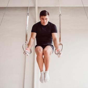 Брюнетка мужчина тренируется на гимнастических кольцах