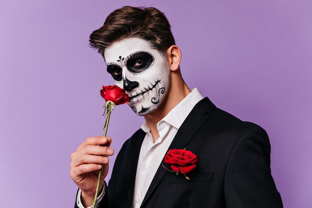 Brunette man in tuxedo posing with rose in halloween. handsome male model with mexican scary makeup standing on purple background.