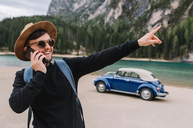 갈색 머리 남자는 강 해안을 따라 산책하는 동안 전화로 말하고 흥미로운 뭔가에 손가락을 가리키는 선글라스와 검은 색 셔츠를 착용