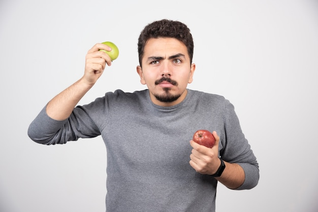 Uomo castana con le mele in piedi sul grigio.