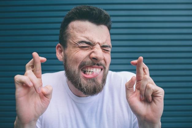 Брюнетка человек с бородой держит глаза закрытыми и показывает зубы. также парень держит пальцы скрещенными. изолированные на полосатый и синий фон.