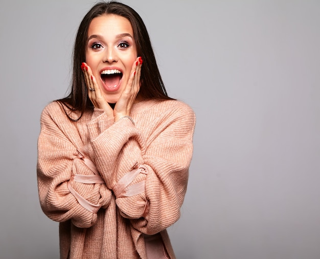 Brunette model in casual beige warm sweater clothes on gray covering her face with hands