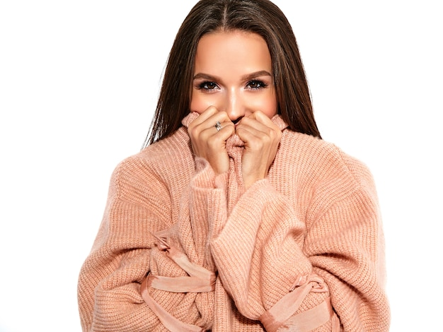 Brunette model in casual beige warm sweater clothes on gray hugging herself