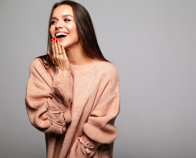 Brunette model in casual beige warm sweater clothes on gray
