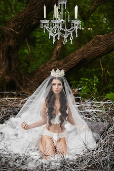 Brunette model girl in lingerie and crown is sitting in a huge nest in the green forest