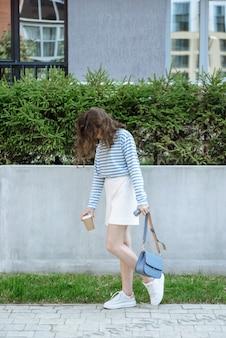 새 컬렉션 옷 카탈로그에서 포즈를 취하는 comme 컵을 가진 갈색 머리 모델 소녀