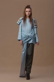 Брюнетка-модель в синей хлопковой блузке и брюках цвета хаки позирует в полный рост на бежевом