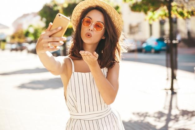 Брюнетка модель в летней одежде позирует на улице с помощью мобильного телефона, давая воздушный поцелуй