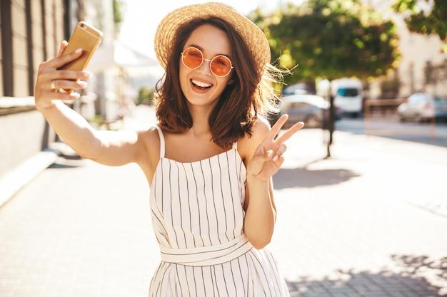 Брюнетка модель в летней одежде позирует на улице с помощью мобильного телефона, показывая знак мира