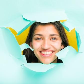 Brunette model posing through paper hole