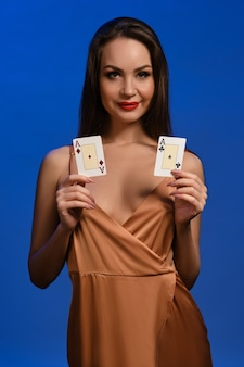 Brunette model in silk beige dress she smiling showing two aces posing against blue wall