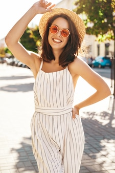 Brunette model in summer clothes posing on the street posing