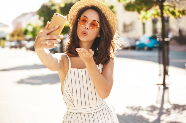 Brunette model in summer clothes posing on the street using mobile phone giving air kiss