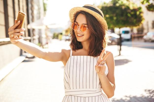 Modella bruna in abiti estivi in posa sulla strada utilizzando il telefono cellulare