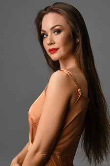 灰色の壁に対して横向きにポーズをとりながら微笑む、明るいメイクと長い髪のシルク ゴールデン ドレスのブルネット モデル