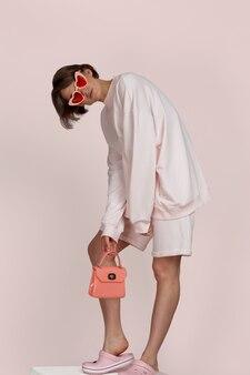小さなバッグとスタイリッシュなピンクのスポーツウェアメガネでポーズをとる短い髪のブルネットモデル