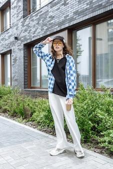 새로운 여름 옷 컬렉션에서 도시 거리를 배경으로 포즈를 취한 갈색 머리 모델 여성