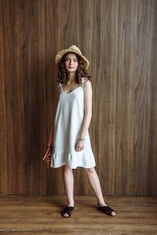 帽子とドレスのスタジオでポーズをとるブルネットモデルの女性