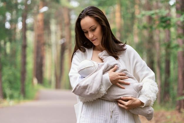 갈색 머리 엄마는 공원, 엄마의 사랑과 관심 개념에서 그녀의 신생아를 안아