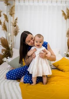 갈색 머리 엄마는 침실에서 침대에 하얀 드레스를 입고 그녀의 아기 딸을 키스