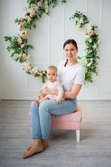 갈색 머리 엄마는 꽃과 흰색 배경에 그녀의 아기 딸과 함께 앉아