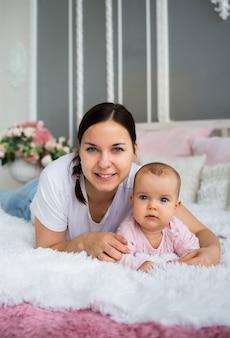 Брюнетка мать и ее дочь лежат на одеяле на кровати