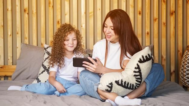 Брюнетка мать и дочь ребенка разговаривают с отцом по видеосвязи, размахивая руками и отправляя воздушные поцелуи, на большой серой кровати у коричневой деревянной стены дома