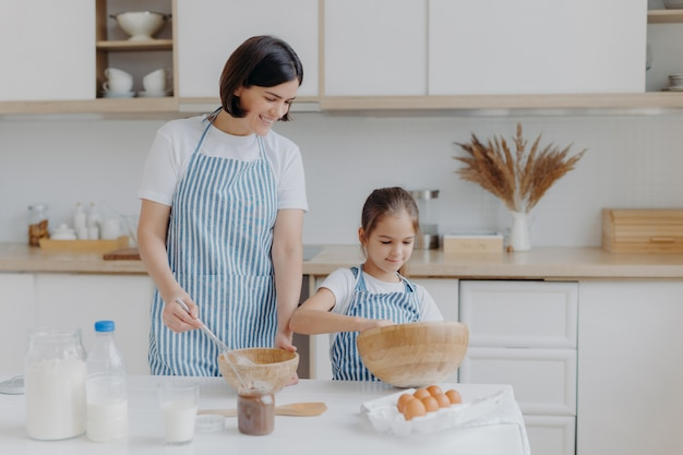 Brunette mother and little kid make cookie dough