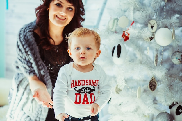 Brunette mother stands behind her little son before christmas tr
