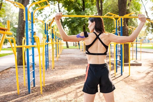 公園、背景のスポーツグラウンドでフィットネス抵抗バンドでポーズをとるブルネットの筋肉の女性。屋外でのボディトレーニングに弾性テーピングを施した若い女性の背面図。