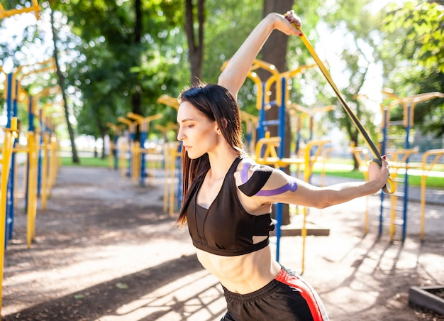 Brunette muscular woman posing with fitness resistance band in park, sports ground. back view of young female with elastic taping on body training outdoors. rehabilitation concept.