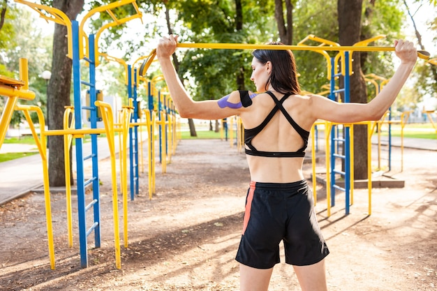 Brunette muscular woman posing with fitness resistance band in park, sports ground on background. back view of young female with elastic taping on body training outdoors.