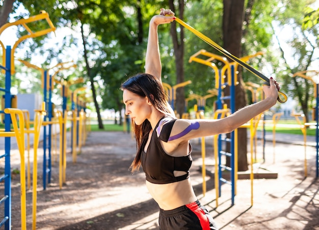Brunette muscular woman posing with fitness resistance band in park