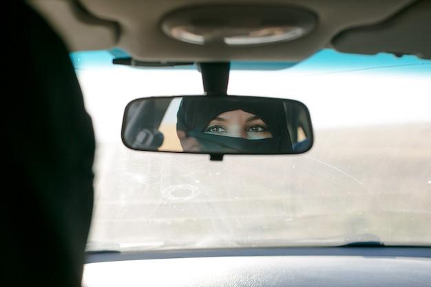 Брюнетка мусульманская женщина в отражении автомобильного зеркала в салоне.