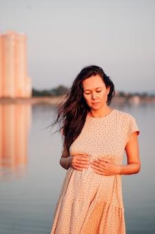都市景観の背景にブルネットシルク水玉ドレスで美しい長髪のアジアの女性...