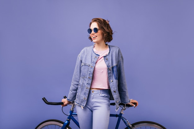 Bruna donna ottimista in occhiali da sole scuri in posa con la bicicletta. ragazza allegra attiva in vestiti di denim in piedi.