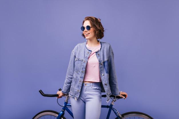 自転車でポーズをとって暗いサングラスでブルネットの楽観的な女性。立っているデニムの服を着たアクティブな陽気な女の子。
