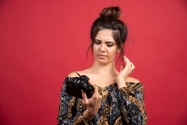 La ragazza bruna della fotografia controlla le sue foto nella fotocamera e sembra insoddisfatta.
