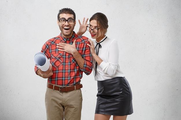 Bruna donna dall'aspetto piacevole guarda attentamente attraverso gli occhiali al suo fidanzato